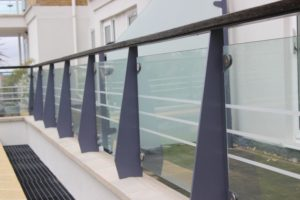Balcony railings in mid blue with wooden hand rail and glass