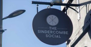 Sindercombe Social pub sign with shadows and streetlamp
