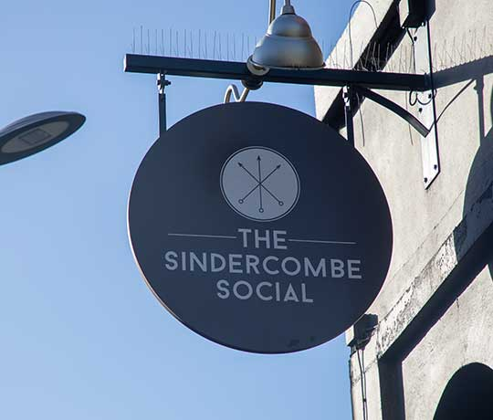 Pub sign Sindercombe Social against blue sky