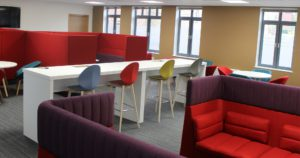 Brightly coloured chairs, white bar, purple and red sofas Tramway