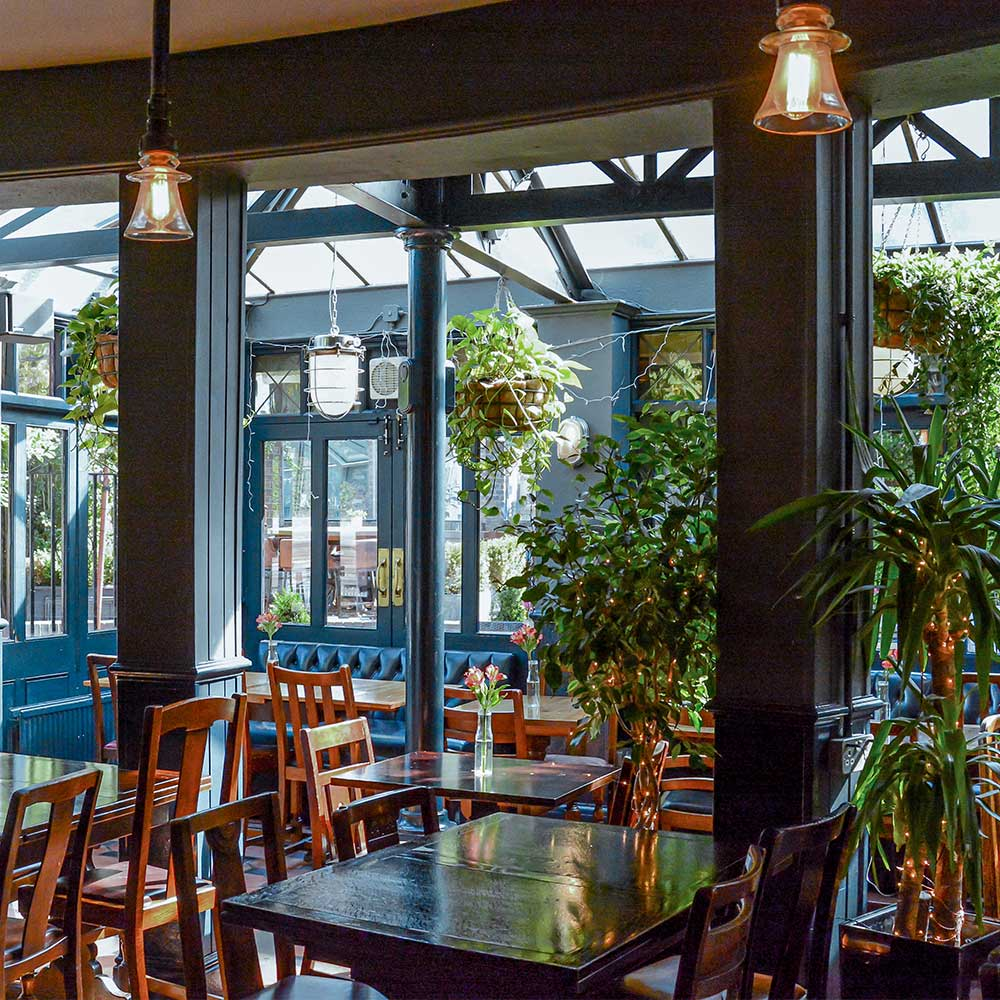 large botanical area of a pub refurbishment tables and chairs in a light area.