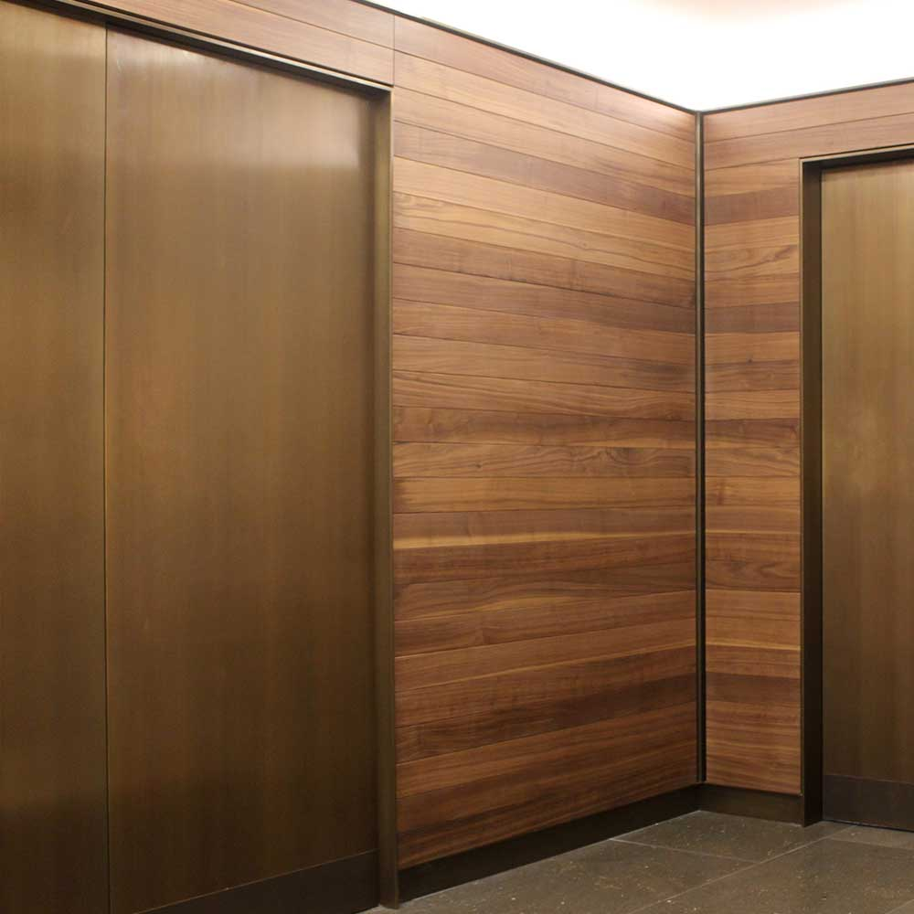 two elevator doors that has been refurbished with a wooden texture.
