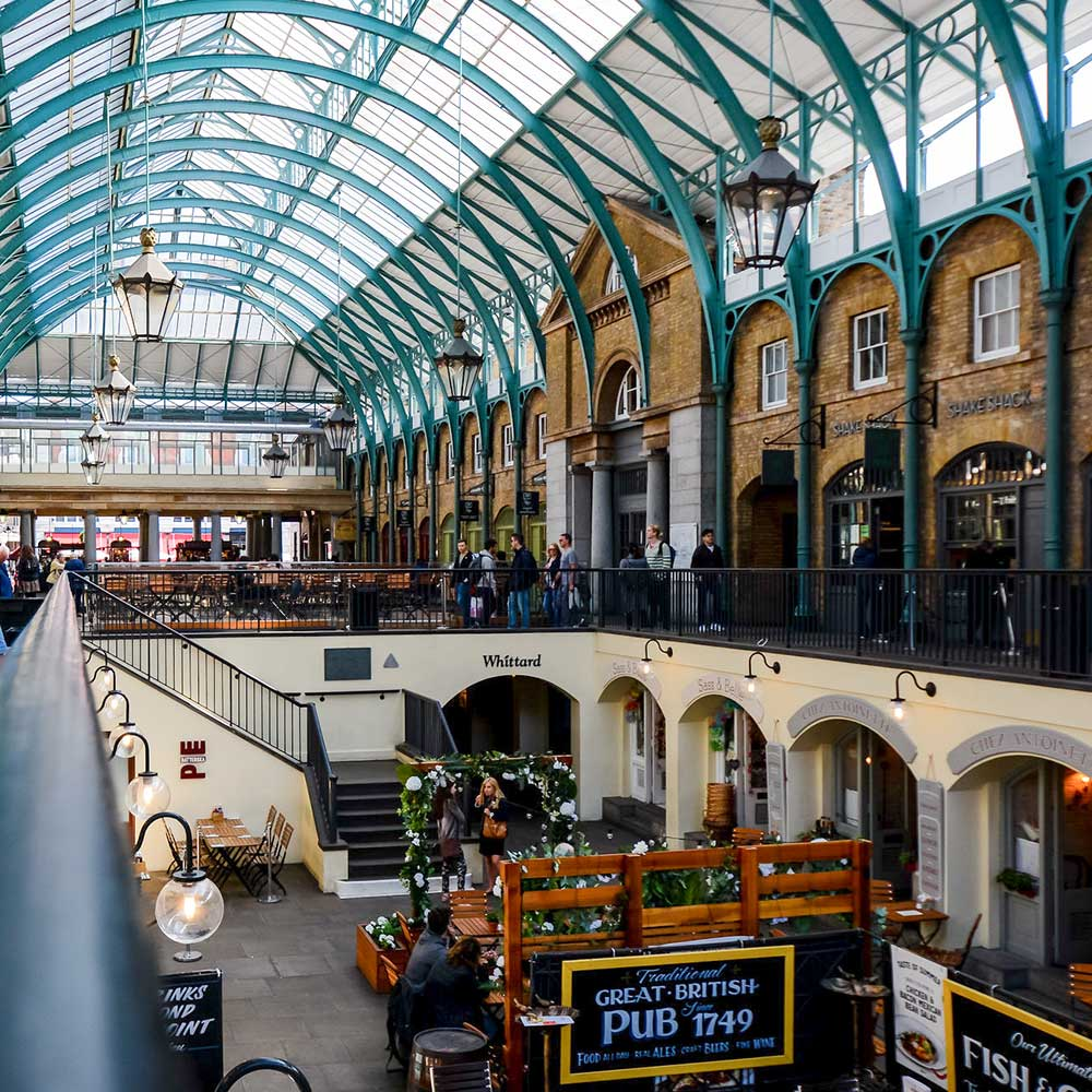 a busy day inside grade 2 listed Covent garden market showing the new restoration including painted roof works