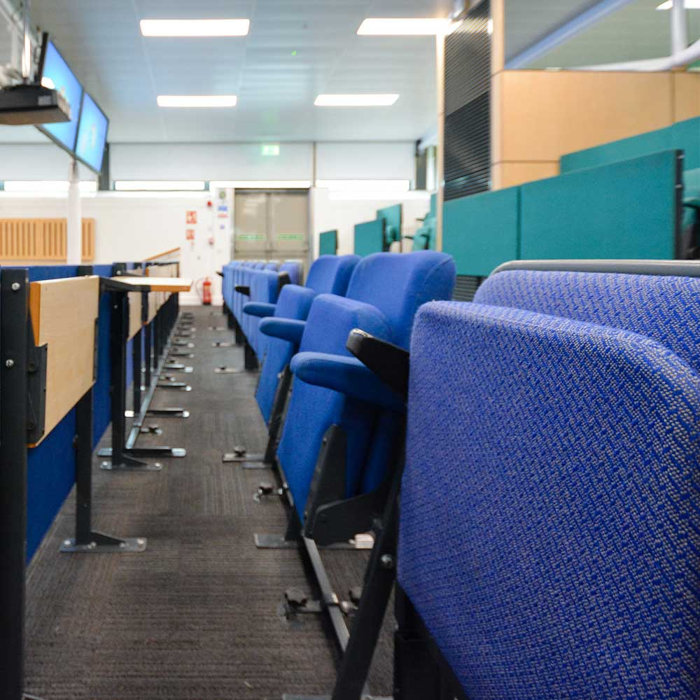 Lecture hall with blue seats inside a university after refurbishment works