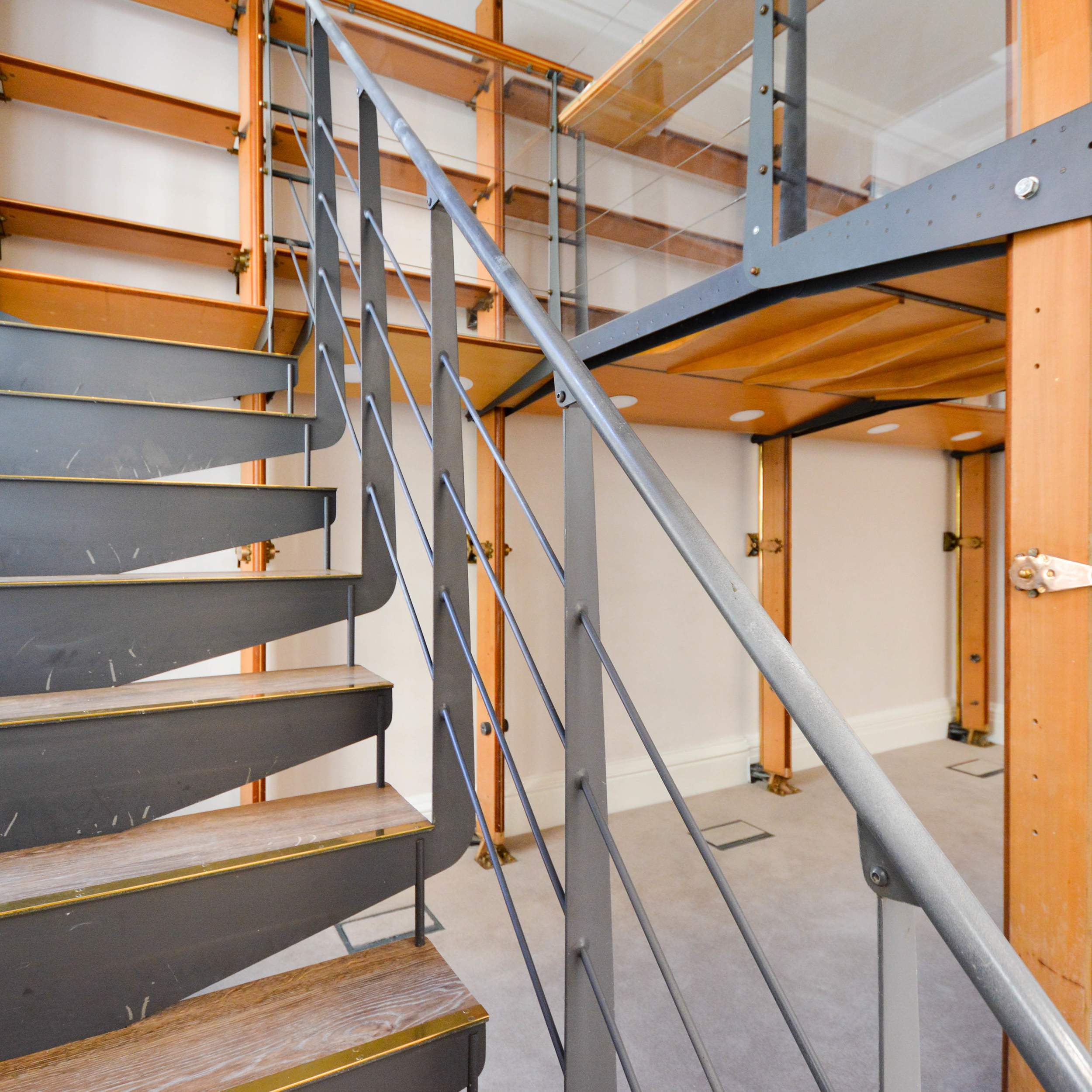 Modern metal staircase with wooden features inside a building renovation