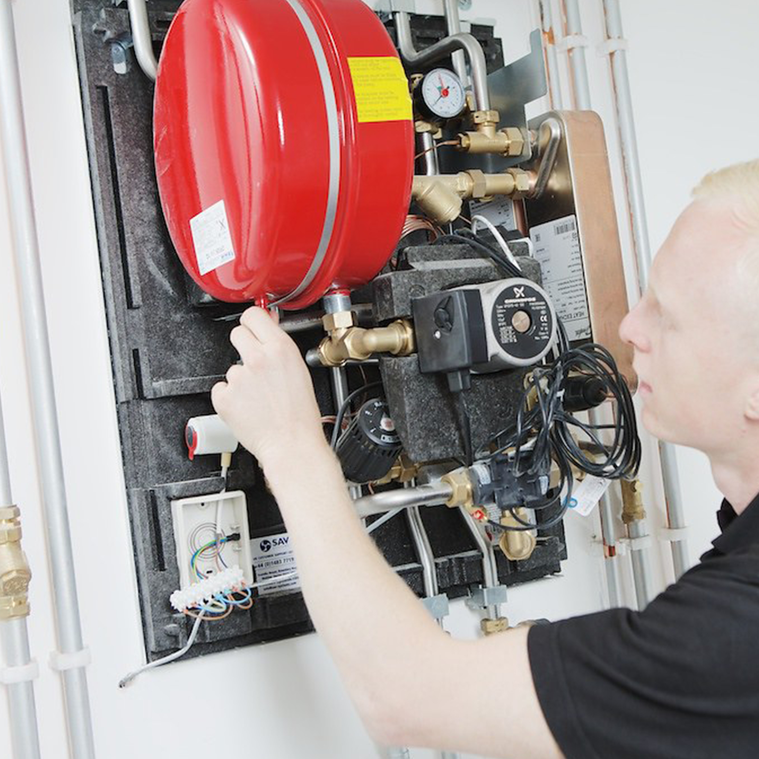 Gas engineer fixing a boiler for compliance