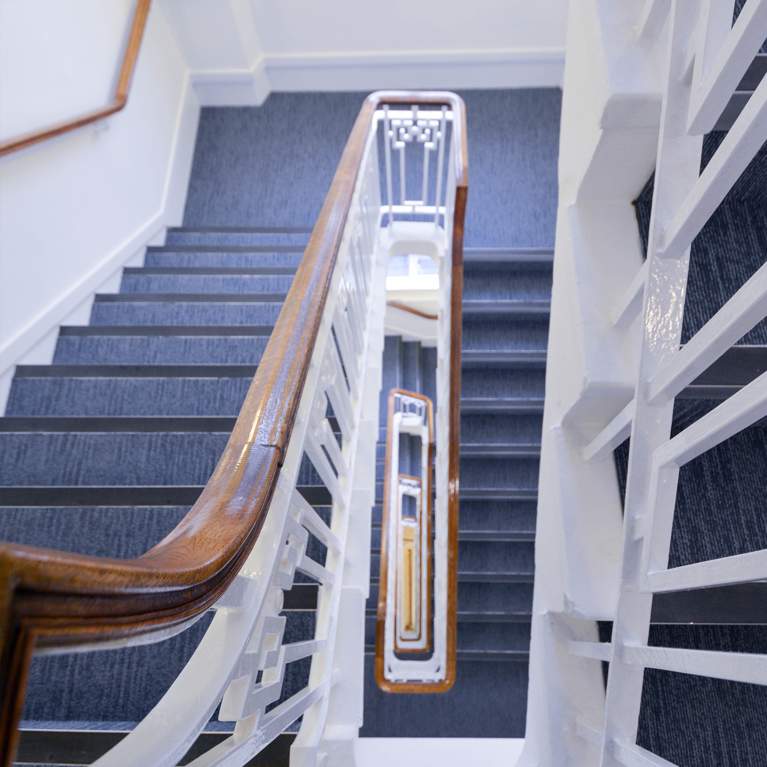 Staircase with wooden banisters and white painted and decorated rails