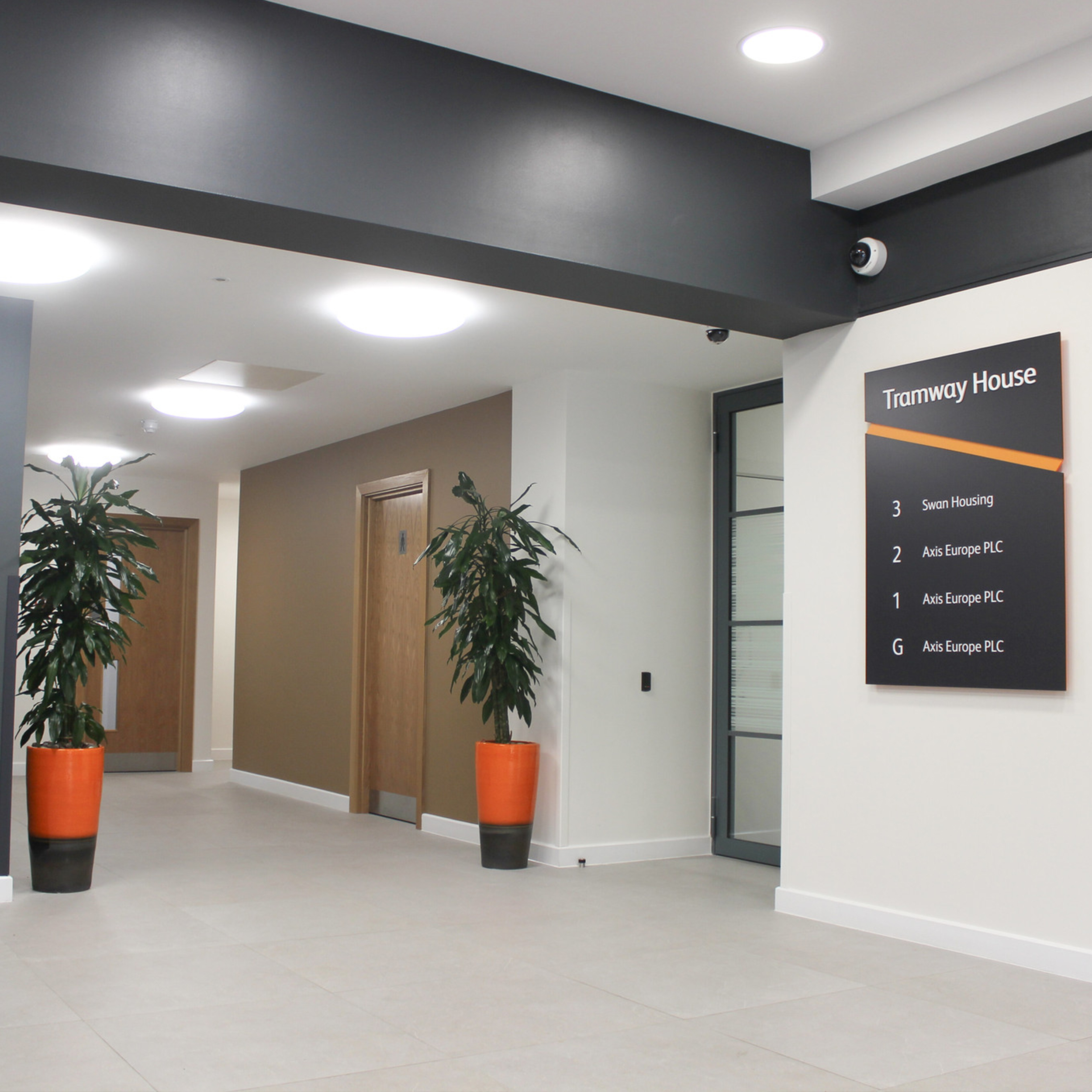 lobby area of a corporate office after refurbishment shows a plant, lifts, new tiles, painting and other renovations