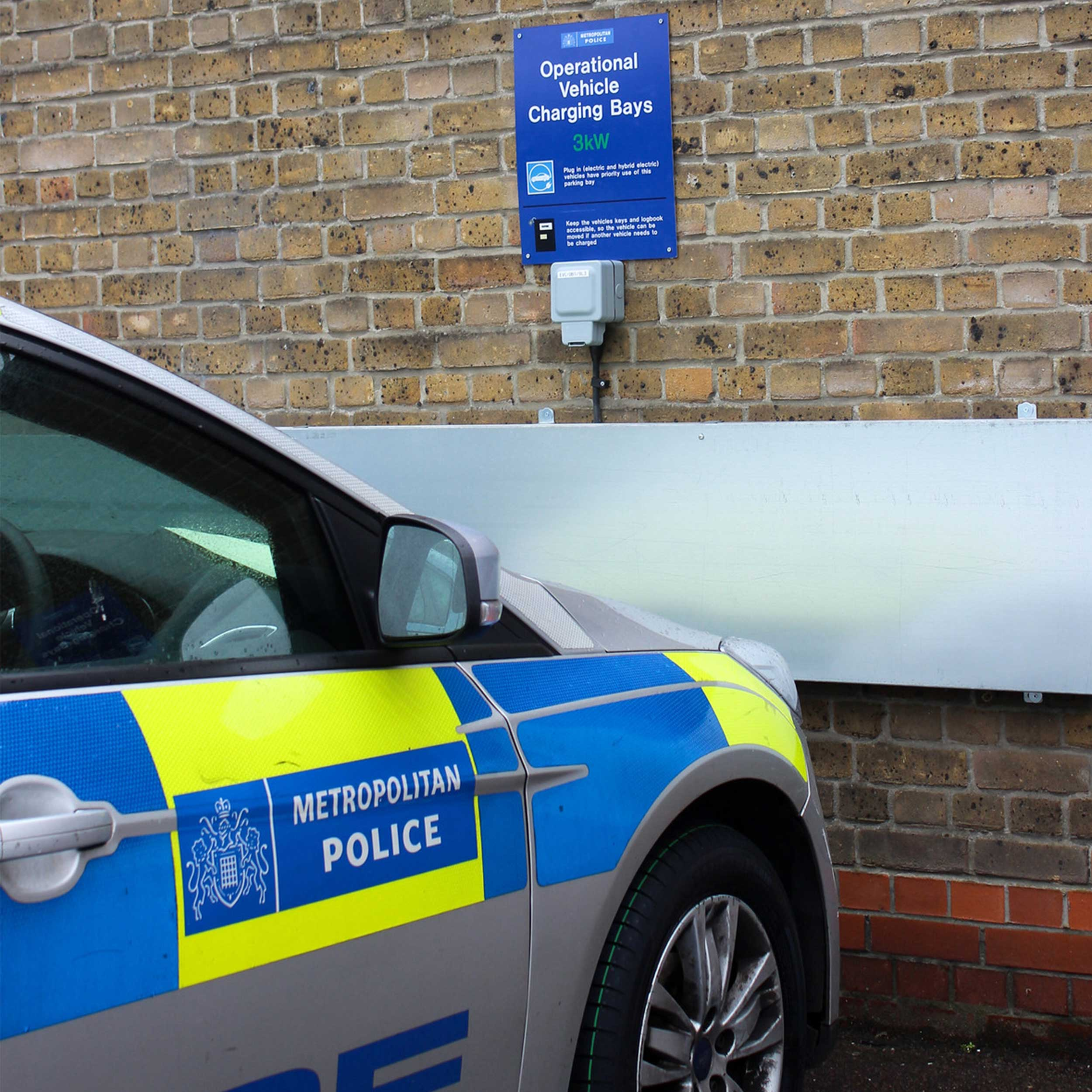 MET-Police-car-charging-in-station-near a brick wall