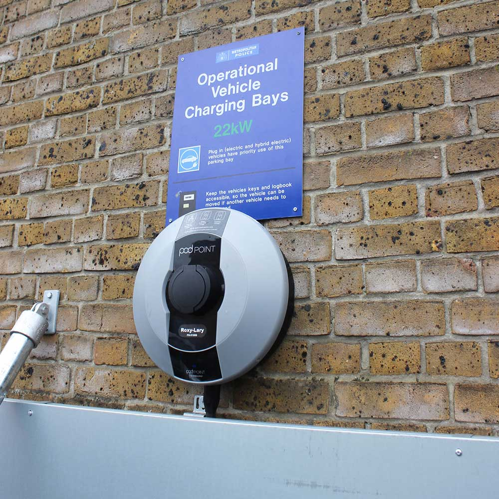 Met-charging-port-close-up-against-brick-wall blue sign included