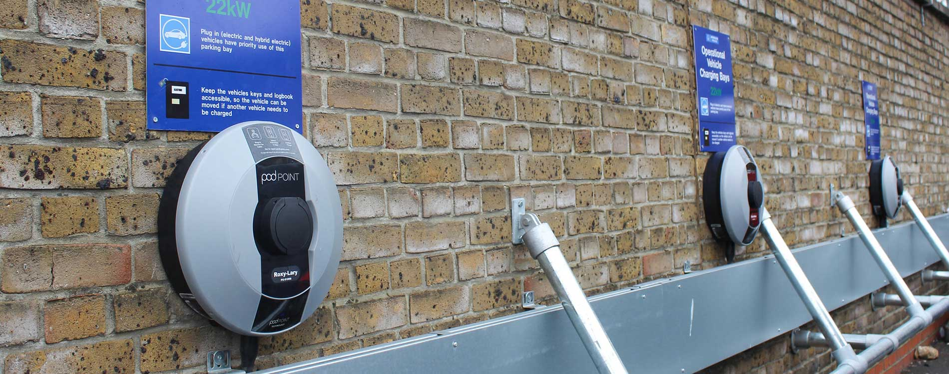 Met-police-electric vehicle charging ports against a brick wall