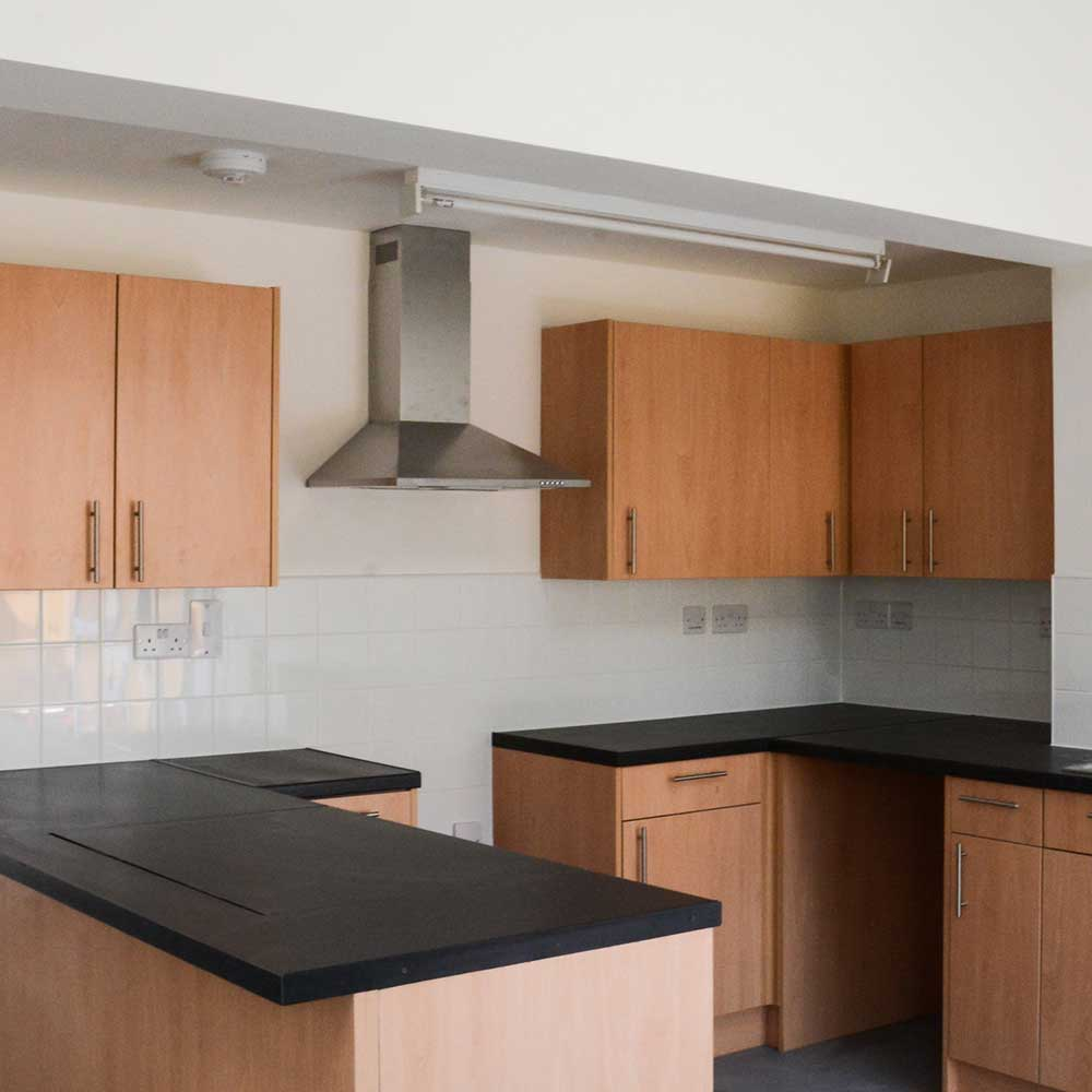 Black worktops inside a new and renovated kitchen space