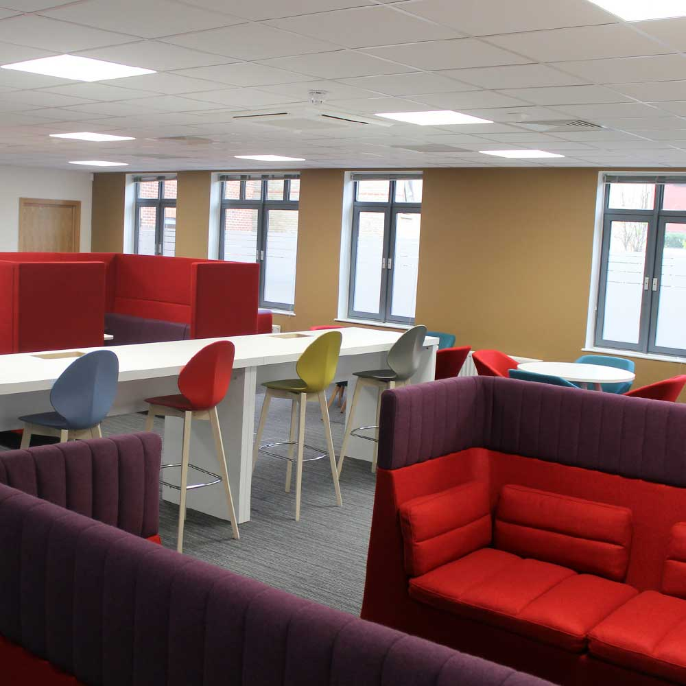 breakout space inside a modern office showing tables and chairs and pods for meetings