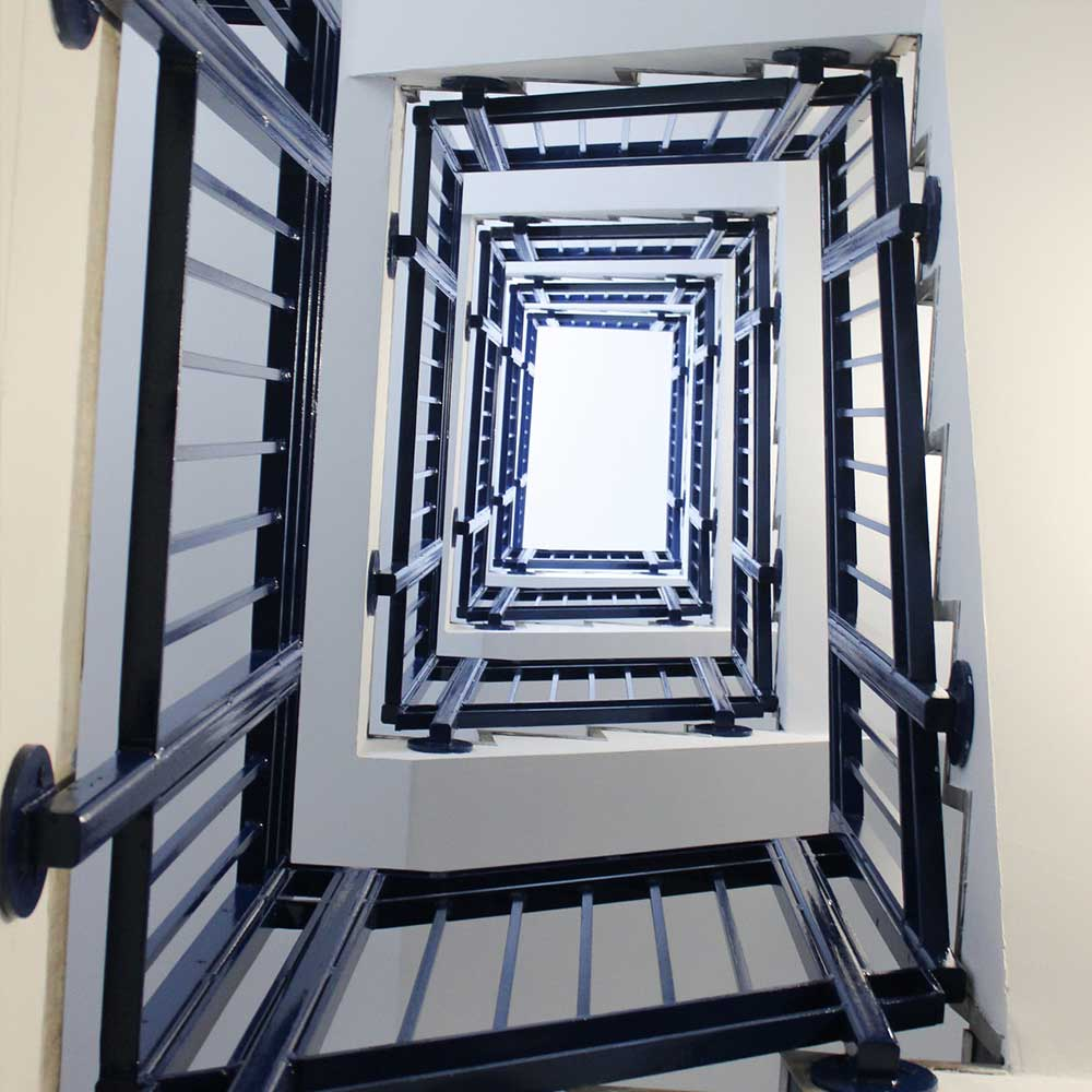 many flights of stairs with new renovations to the banister and railings such as blue paint finish