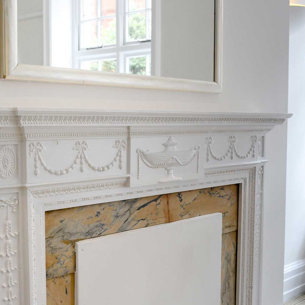 White fireplace with decorative design after conservation works were carried out