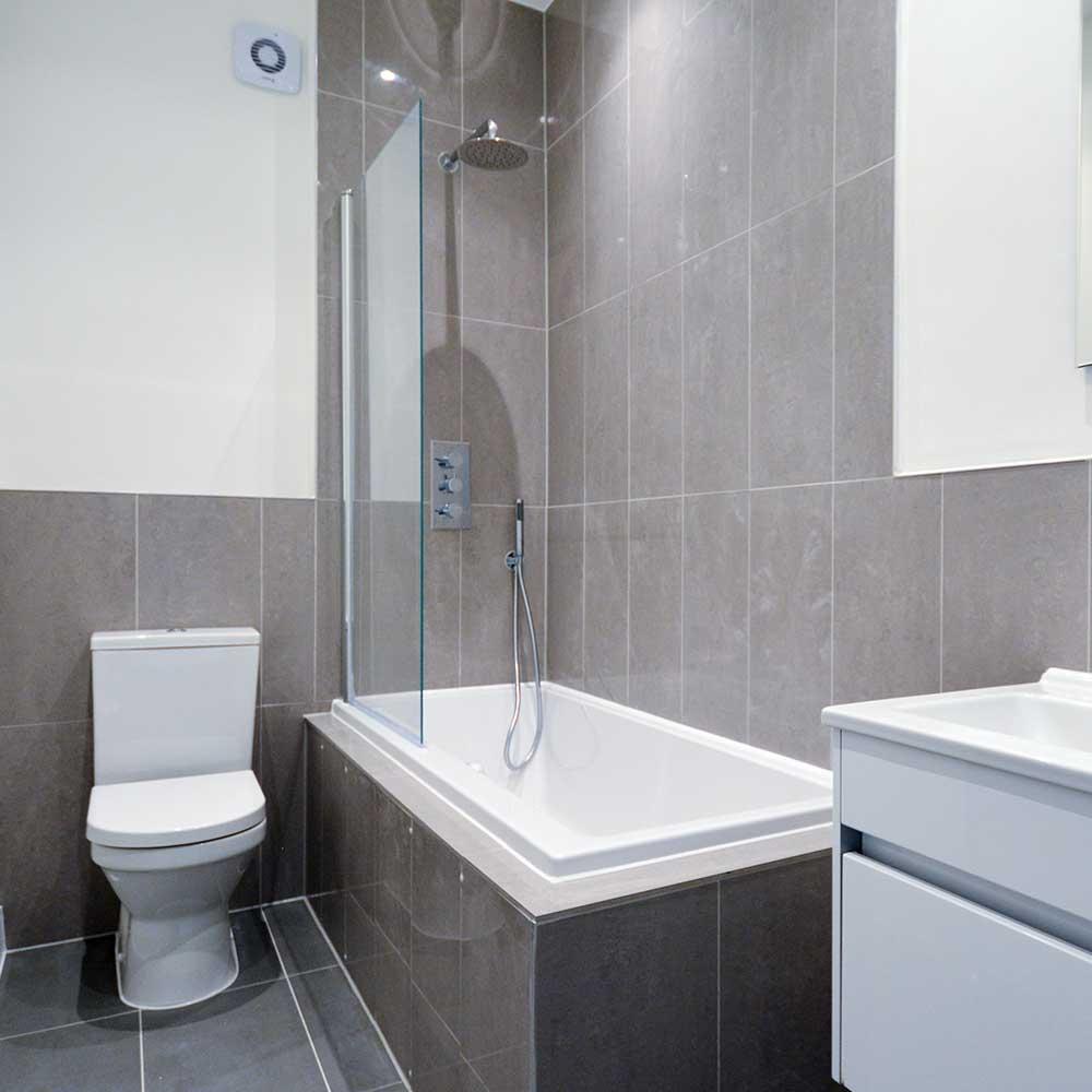 Bathroom with tiled walls inside a refurbished property