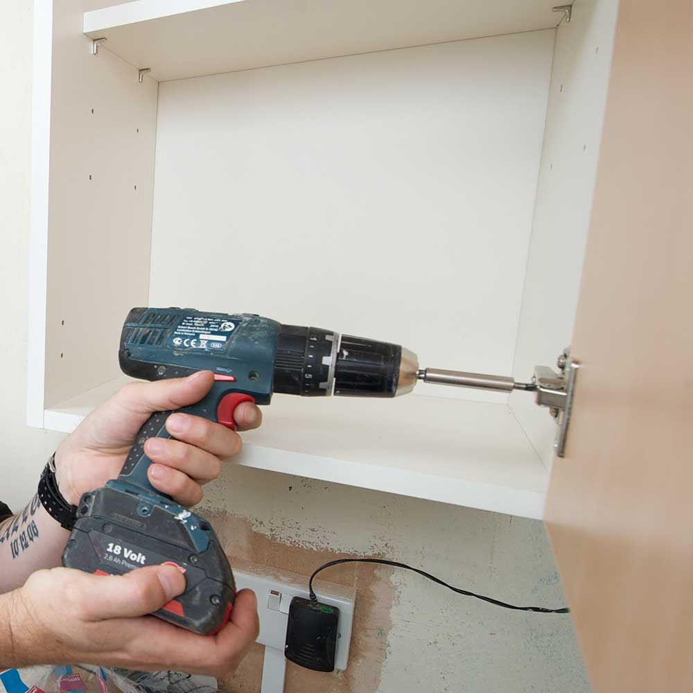 Axis operative tightening the screws in a cupboard as part of compliance service