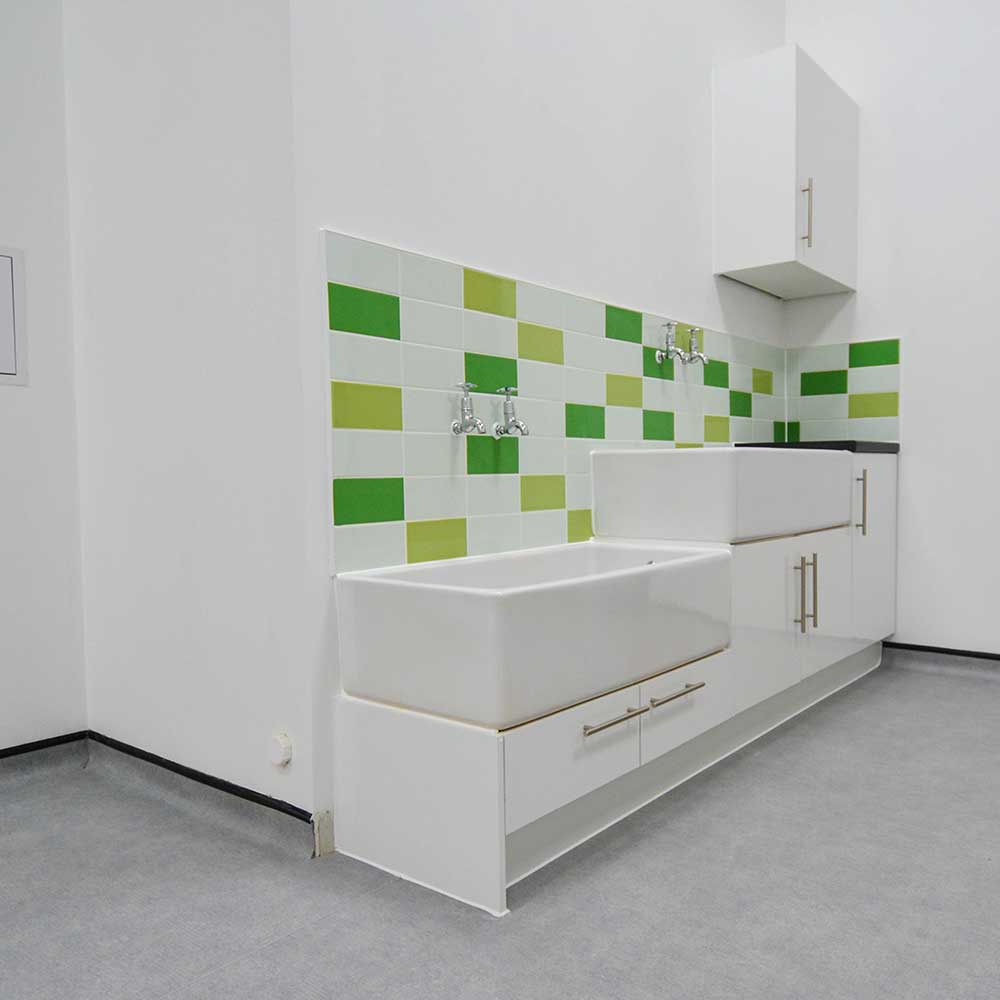 Sinks with green and white tiles behind them refurbished by axis