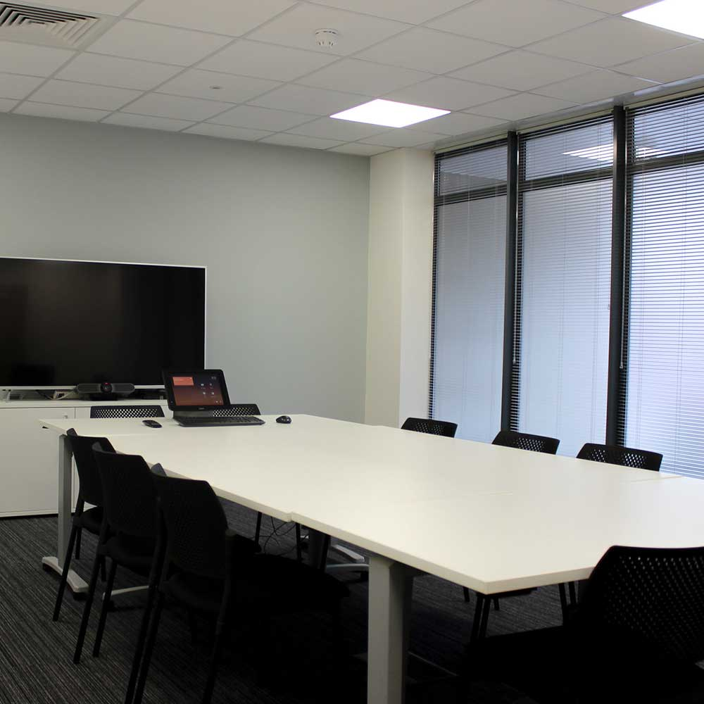 large renovated modern meeting room with digital appliances and a big television screen. new carpets and painting.