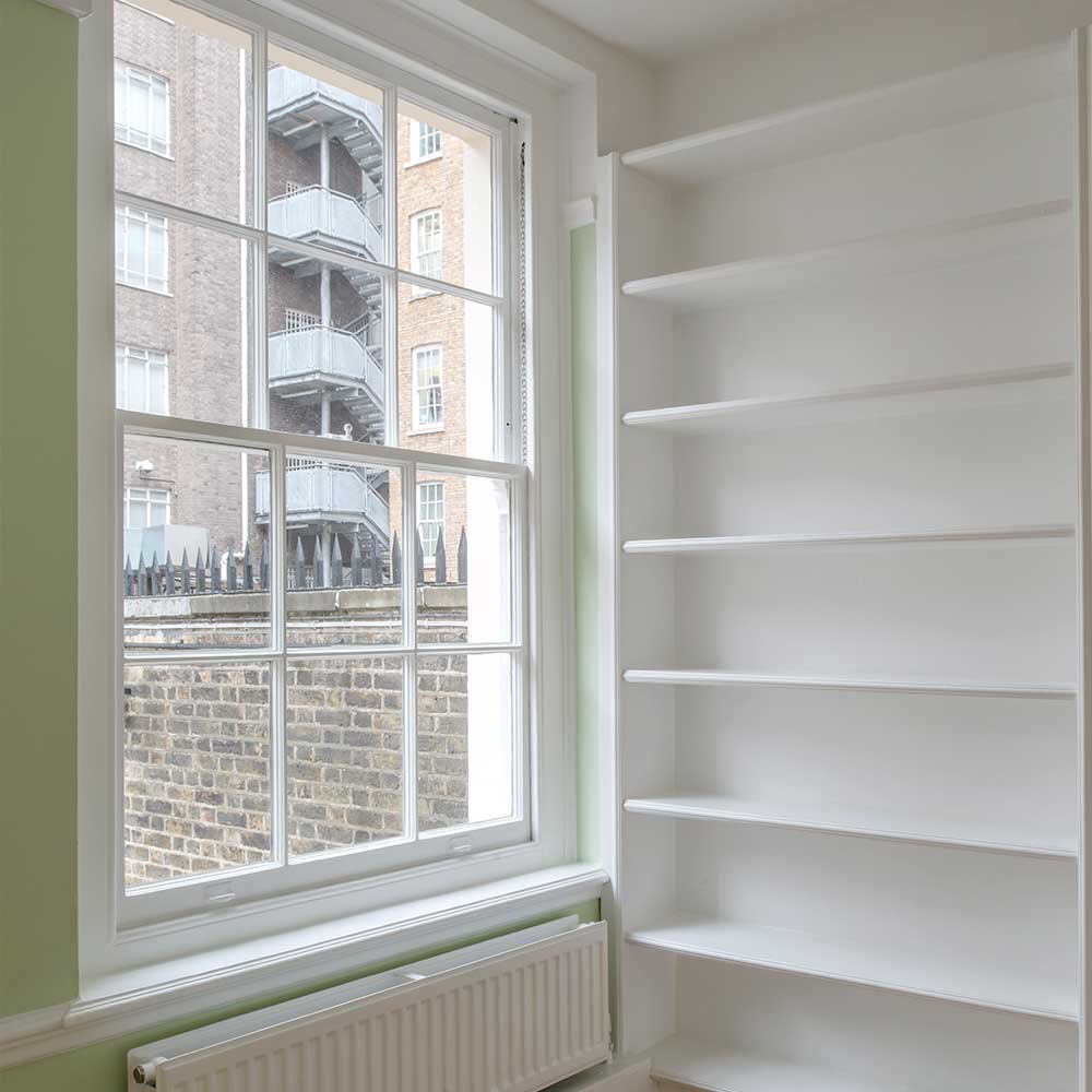 Window and bookshelf inside a repaired grade 2 listed building