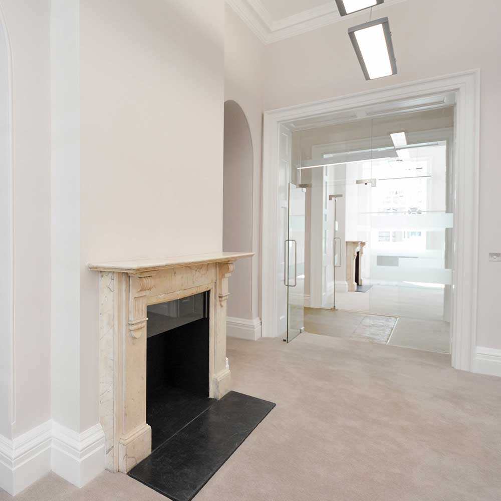Open bright space with a fireplace inside a heritage building