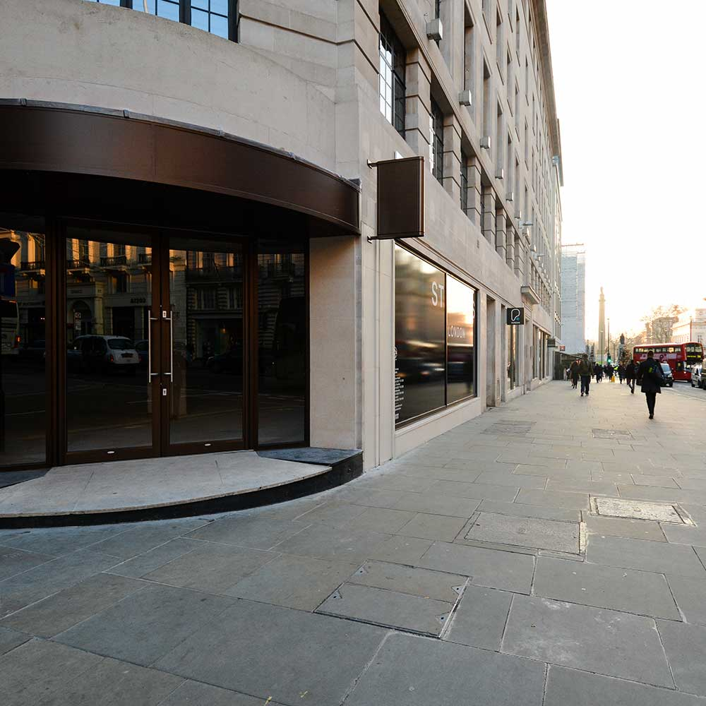 Busy London street with pedestrians walking by a a refurbished office