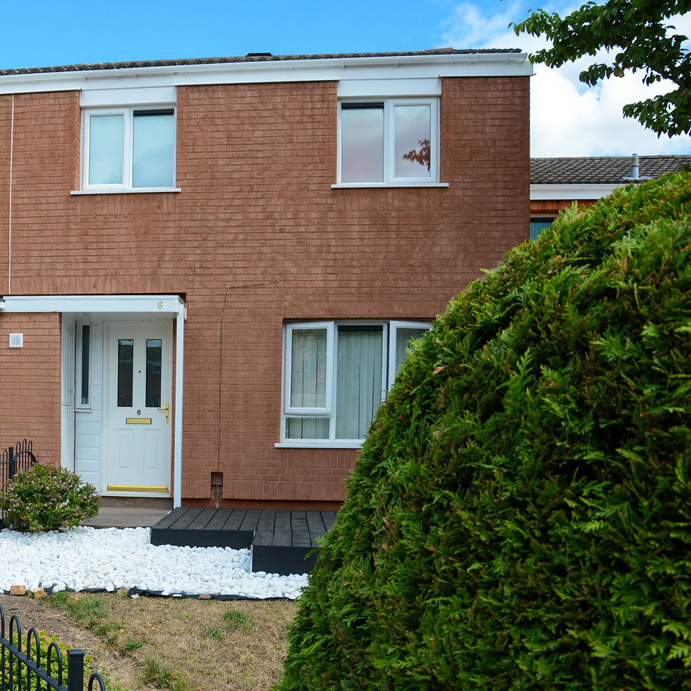 a residential property with new insulation to the exterior a small garden and a patio space