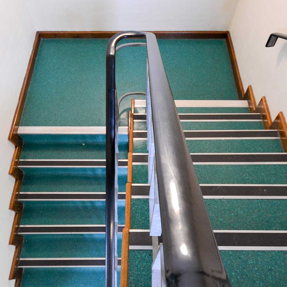 Staircase inside a housing property with new banister and green flooring