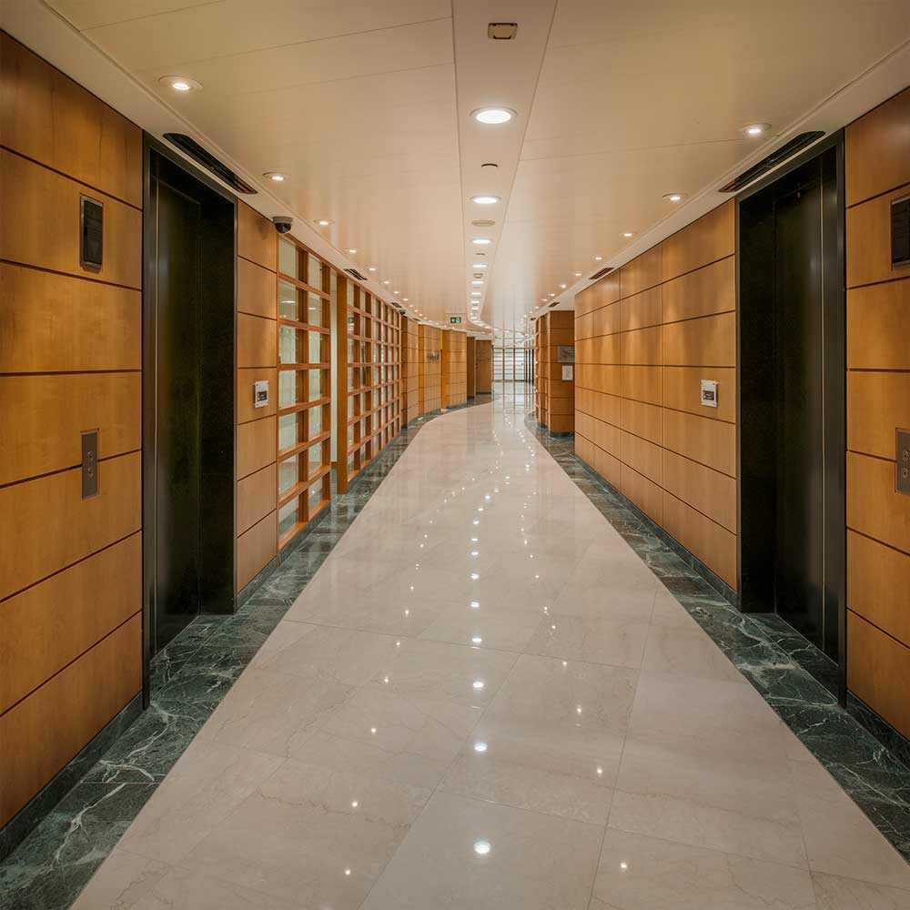 Large marble floored corridor flanked by upgraded lifts.