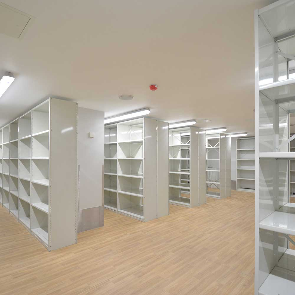 a room filled with shelves and a wooden floor inside a met police public sector building