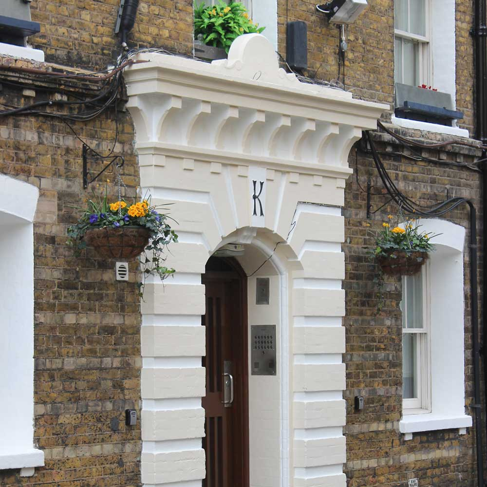 hanging baskets filled with flowers next to an arched doorway at a renovated period property