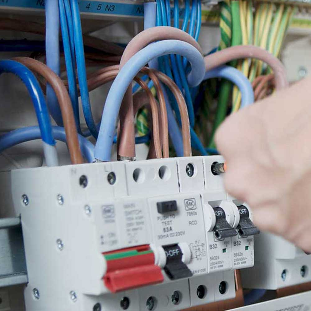 Electrician working with a fuse board as part of housing compliance