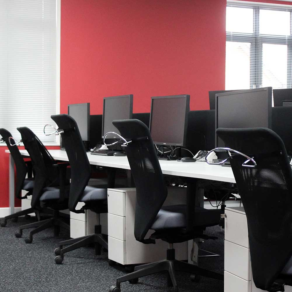 a row of desks with computers and chairs inside a freshly renovated office space in east london