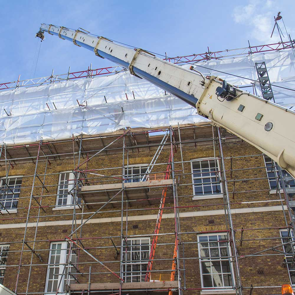 Scaffolding and a crane as renovation works take place on a heritage building