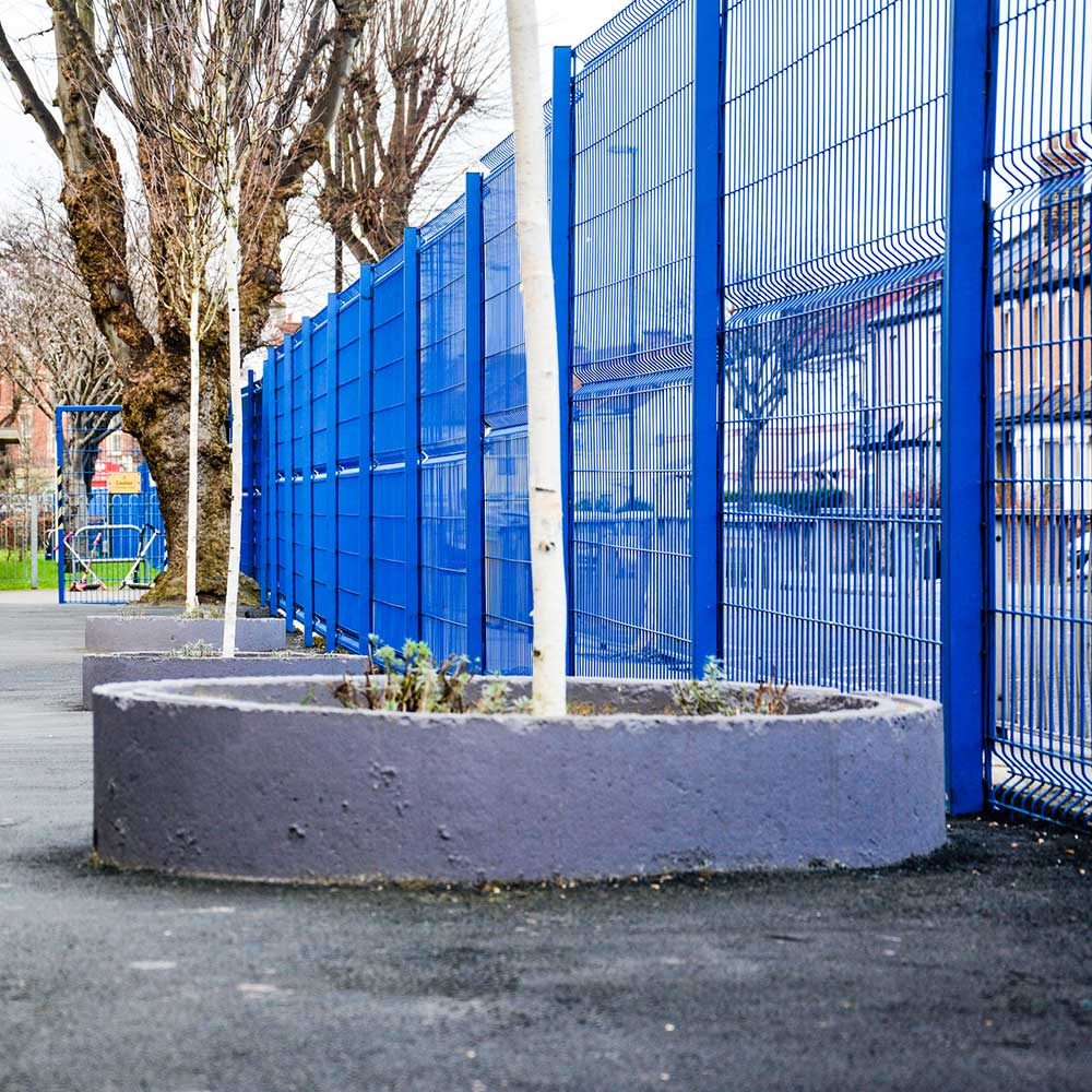 Blue fence and planters with a tree in a school playground that axis renovated