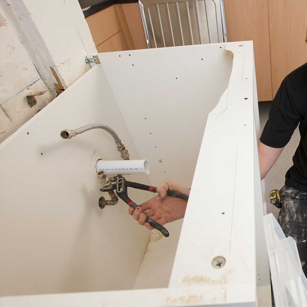 Axis plumber works on pipes as part of a housing compliance services contract