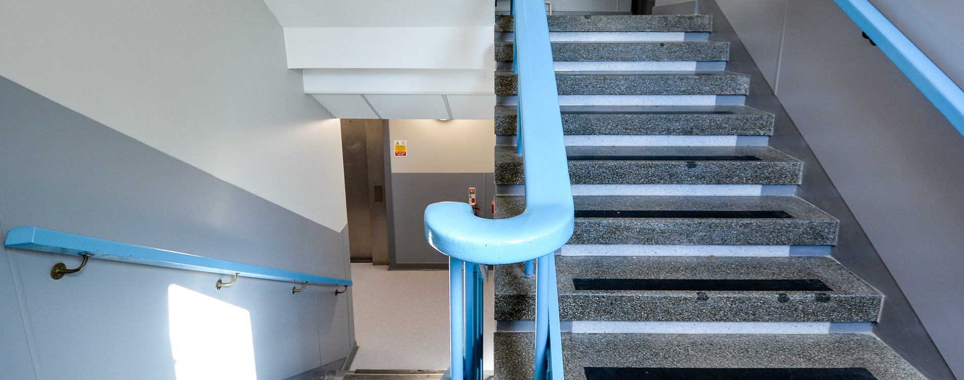 Staircase with a blue painted rail inside a police station refurbishment