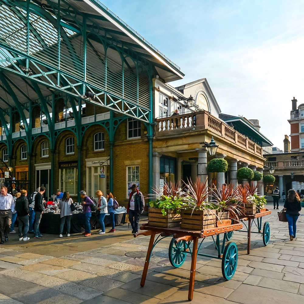 covent-garden-front-with-flowers on a sunny day shows building restoration works to the London landmark are shown
