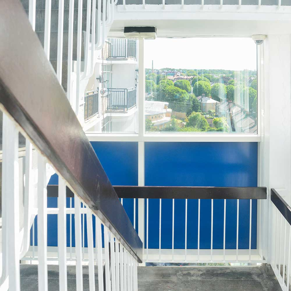 staircase inside a block of flats that shows leafy suburban London and the refurbishment works on the staircase