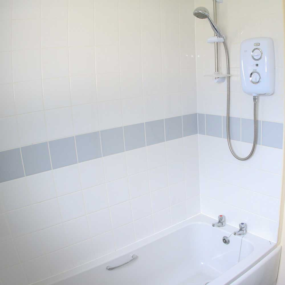 Bathroom with a bath and shower inside a property that axis undertook refurbishment works