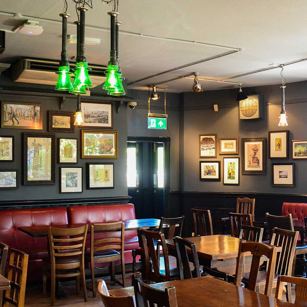 Large open room filled with tables and chairs in a pub refurbishment