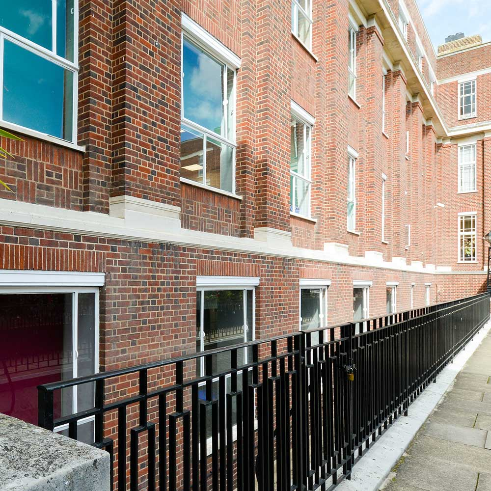 a new painted rail next to refurbished building and brickwork