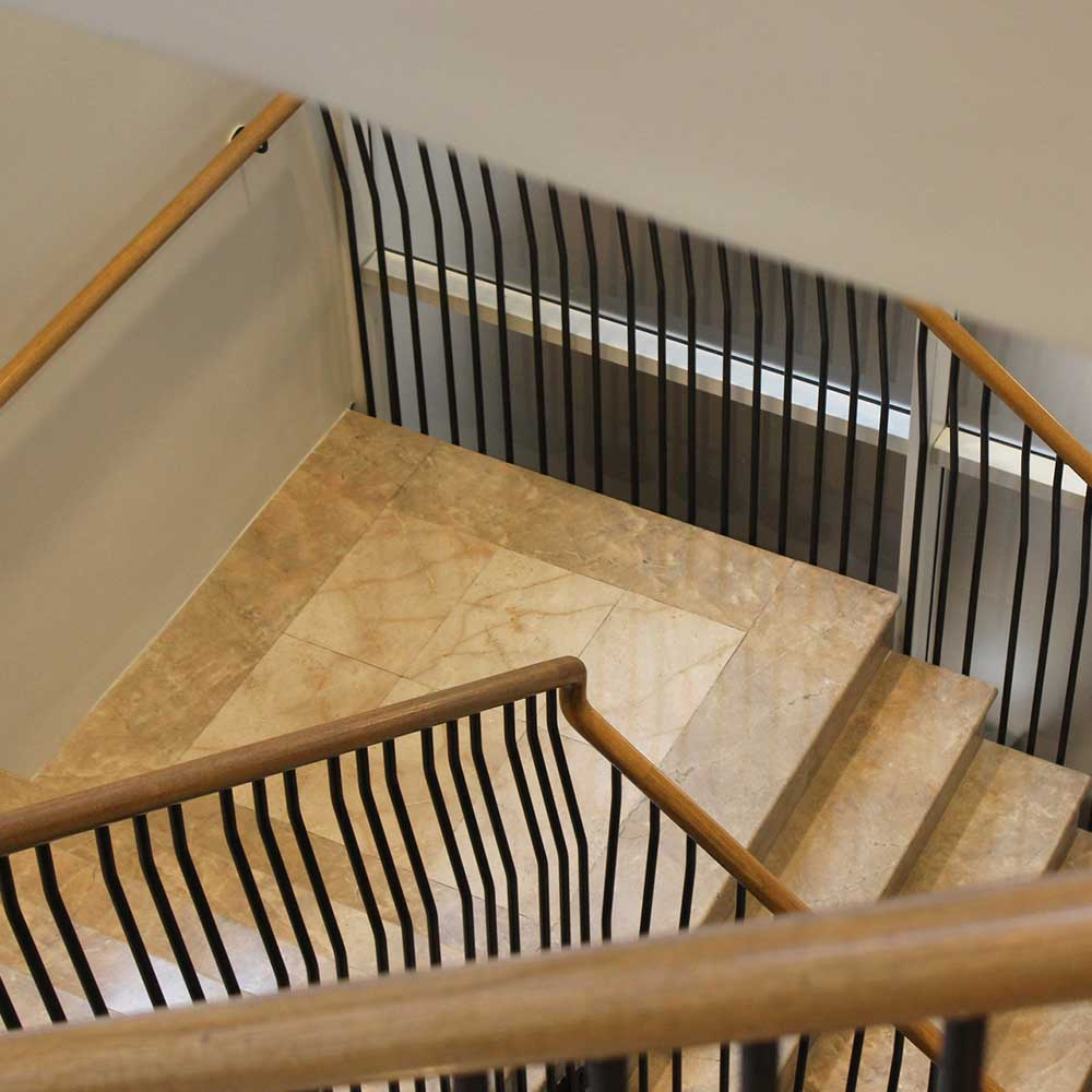 Staircase with a wooden rail and black painted banisters inside a listed building