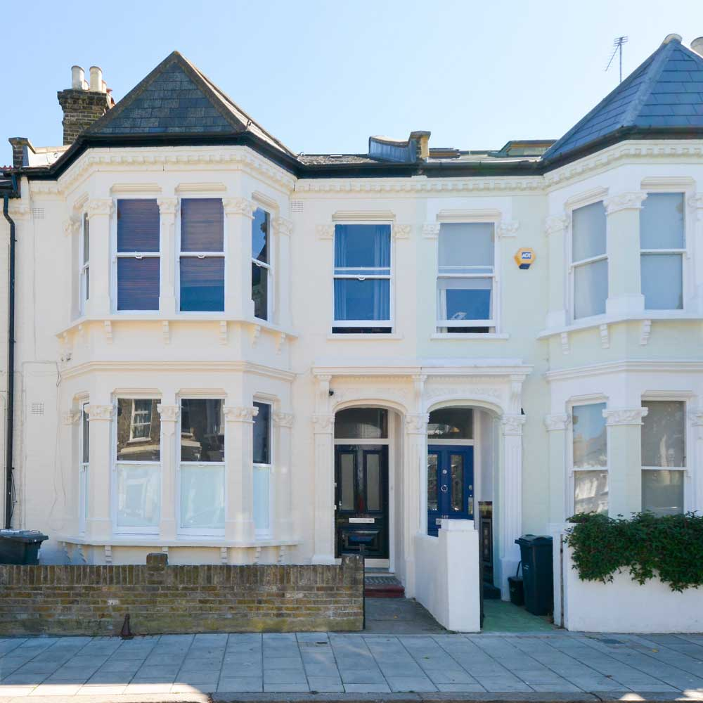 two terrace houses side by side on a street in London they have a white paint exterior after cyclical decorations