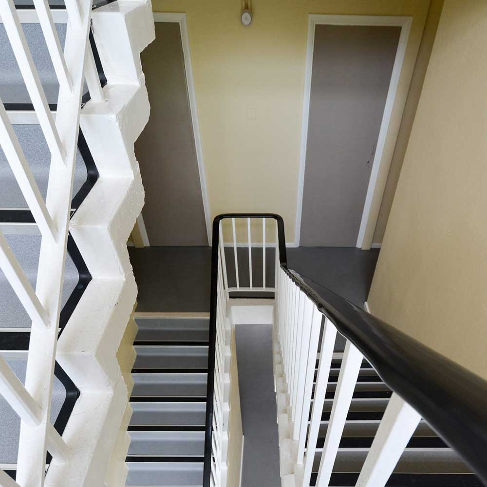 Large staircase with a white painted and decorated banister after refurbishment
