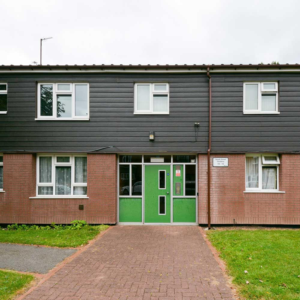 Exterior of a block of flats with a green door that axis refurbished
