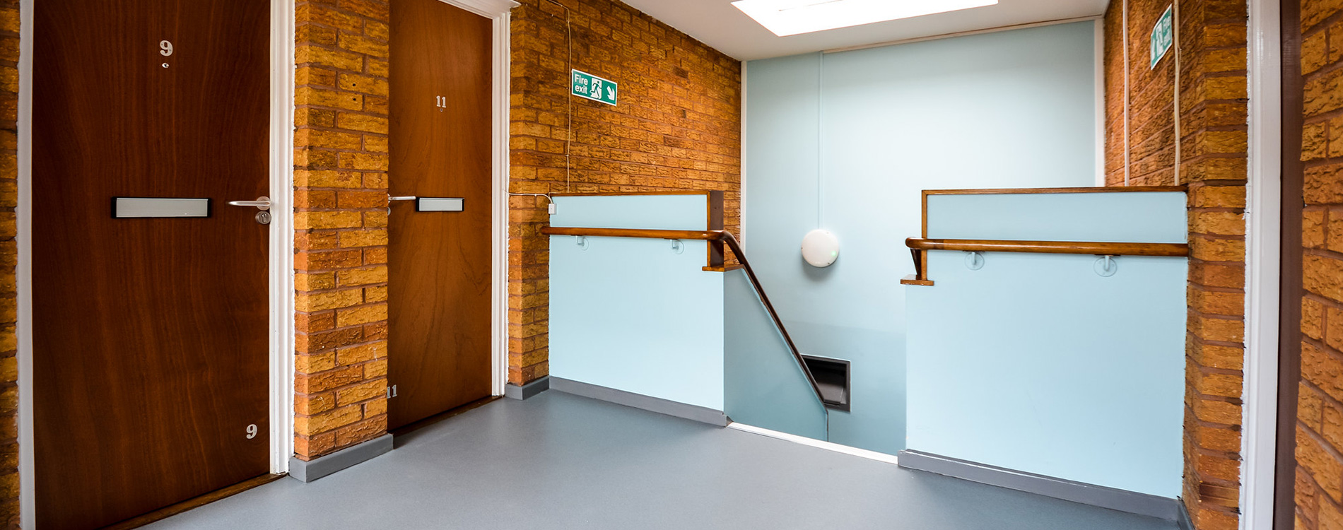 Staircase inside a residential property refurbishment shows a landing area with blue painted walls and new door installation