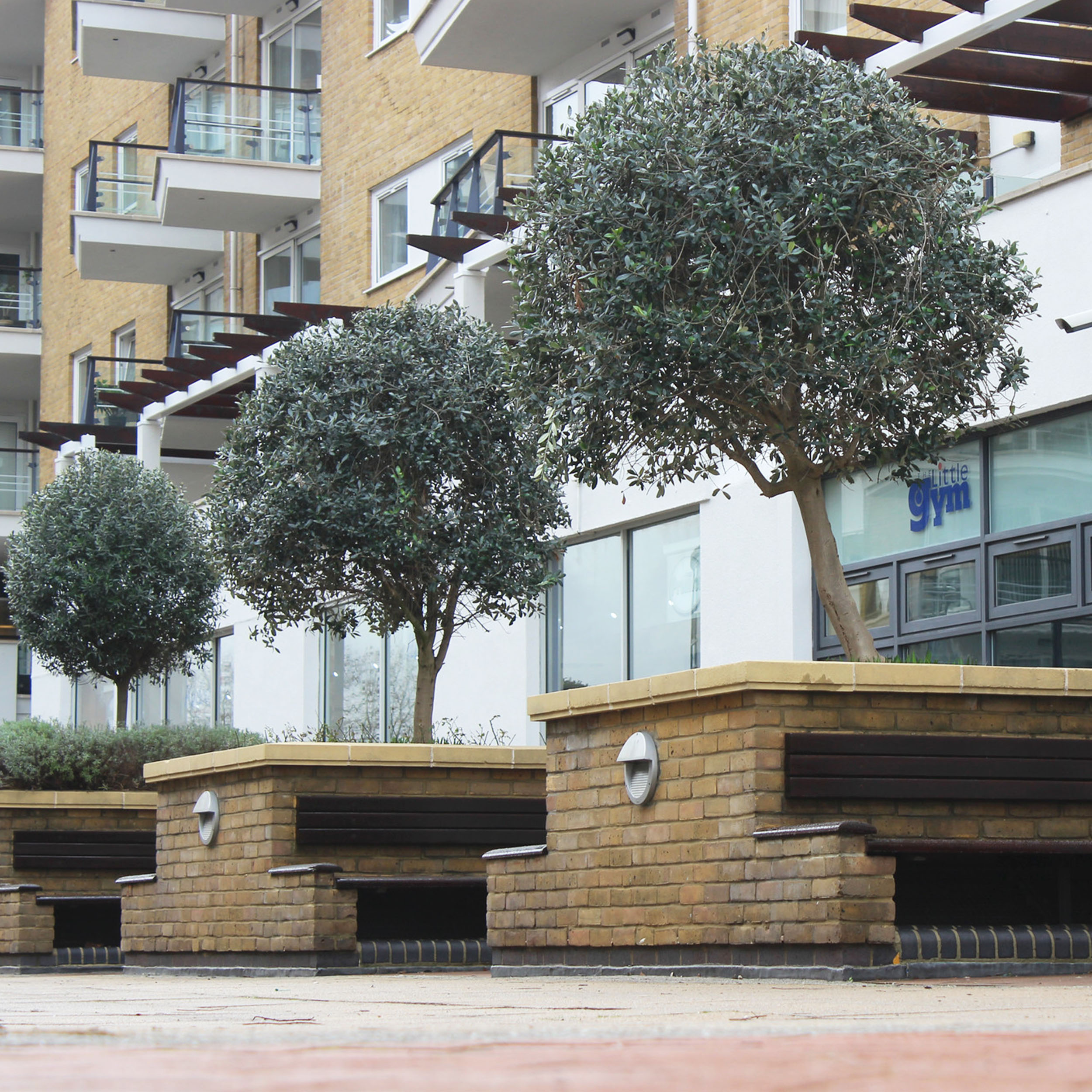 Forecourt of a private housing area shows the new brickwork and painting applied to benches and planters