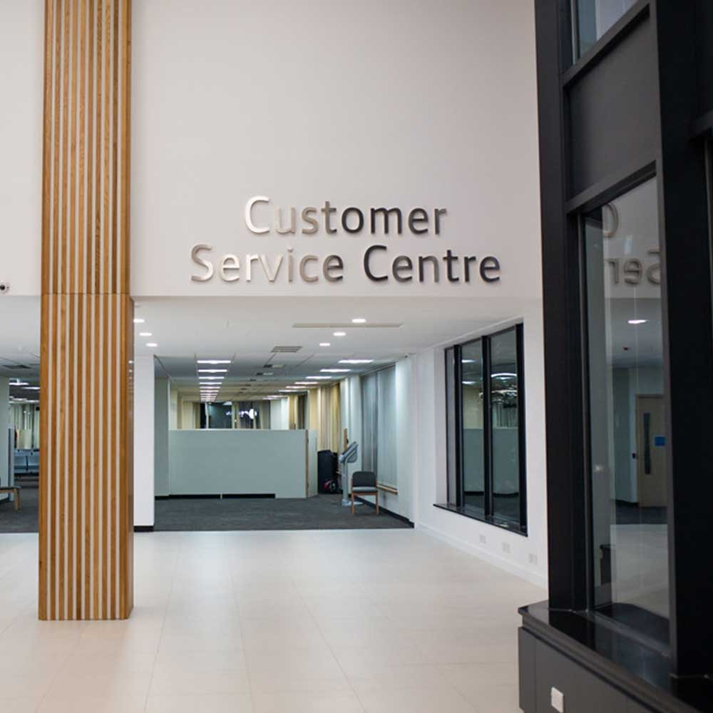 Customer service center sign against a freshly painted and decorated white wall
