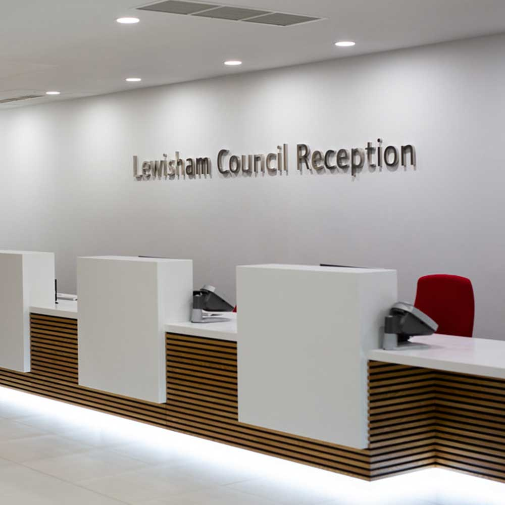 refurbished council reception desks with red chairs and white walls